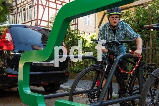 Fünf Bügel zum Anschließen von Fahrrädern auf dem Parkraum eines Mittelklasse-Autos bietet diese stabile Abstellanlage.