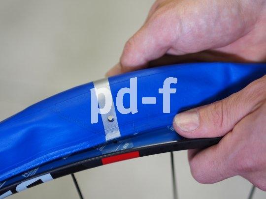 Der 4. Schritt: Der blaue Procore-Innenreifen wird mit einer Seite ins Felgenbett gezogen, ganz wie bei der normalen Reifenmontage. Der silberne Streifen wird am Ventilloch positioniert, über das kleine Loch wird später die äußere Kammer aufgepumpt.