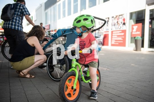 Ein Kinderanhänger mit großem Kofferraum bietet Platz auch für das Laufrad.