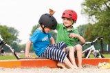 Ein gutes Zeichen dafür, dass der Kopfschutz nicht als Fremdkörper empfunden wird: Beim spiel lassen die Jungs ihn einfach auf dem Kopf. Doch wenn es aufs Klettergerüst geht, müssen Mama und Papa intervenieren.