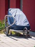 Eine passende Faltgarage schützt den Kinderanhänger vor Wind und Wetter.