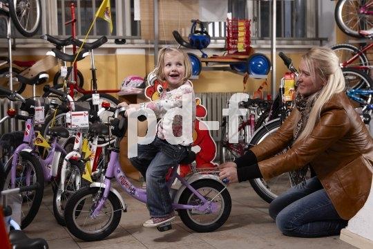 Sitzprobe auf dem ersten Fahrrad: der Sattel sollte niedrig genug sein, damit das Kind locker mit den Füßen auf den Boden kommt. Bei den ersten wackeligen Fahrversuchen sorgt das für Sicherheit.