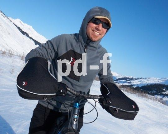 """Die """"Williwaw-Pogies"""" von Hersteller Revelate Designs sind keine klassischen Handschuhe, sonder lenkerfeste Handwärmer, in die man beim Losfahren hineinschlüpft. Sehr praktisch und warm. Sind sie zu warm, lassen sich vorn kleine Belüftungsreißverschlüsse öffnen."""