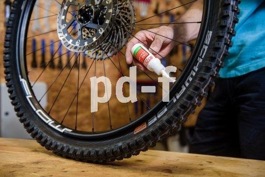 Über die spitze Kappe der kleinen Flasche wird die Dichtmilch durch den offenen Ventilschaft in den Reifen eingefüllt.