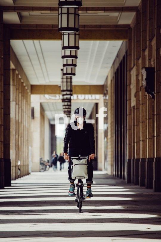 Ein Mund-Nasen-Schutz passt auch gut unter den Fahrradhelm.