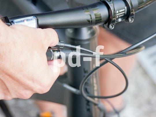 Durch das Drehen an einer Rädelschraube am Schalthebel wird bei einer Nabenschaltung die Spannung im Schaltzug verändert.