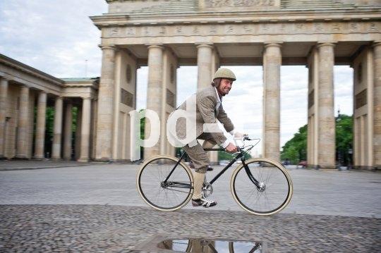 Radeln im Retro-Look vor klassischer Fassade. Zum stimmigen Outfit gibt es nun auch den passenden Helm mit Wollüberzug; so gesellen sich moderne Sicherheitsansprüche zur Freude an der guten alten Zeit.