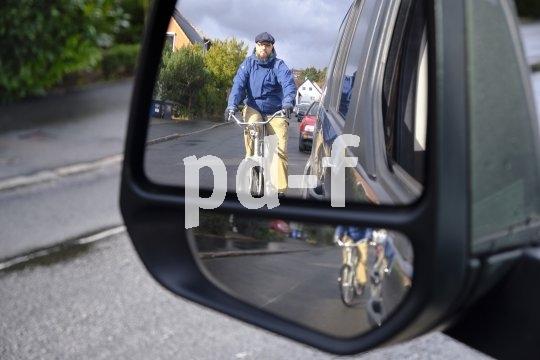"""Gefährlich, wenn der Autofahrer jetzt unvermittelt die Tür öffnet. Der """"Holländische Griff"""" hilft. Hier greift der Autofahrer mit der rechten Hand zur Tür. Der Körper dreht sich automatisch zum Schulterblick: Radfahrer werden nicht mehr so leicht übersehen, gefährliche """"Dooring""""-Unfälle seltener."""