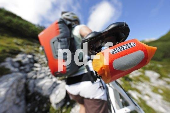 """Sportliche Tourenbiker verteilen ihre """"Essentials"""" auf den Bike-Rucksack und die Satteltasche."""
