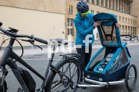 """Da drin ist gut schlafen: Der Kinderanhänger """"Kid plus for 1"""" von Croozer ist mit einer sich automatisch dem Gewicht anpassenden Federung ausgestattet, zudem mit einer dämmerungsgesteuerten Beleuchtung. Er lässt sich leicht zum Buggy oder Jogger umbauen und passt an alle gängigen Fahrradtypen (hier das Modell """"E-Gadino"""" von Stevens)."""