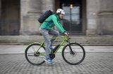 Modernes Radpendeln mit modischem E-Bike und wasserdichtem Rucksack.