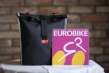"""Eine pfiffige Einkaufstasche, die sich gut mittig falten und verstauen lässt, beladen aber auch am Gepäckträger befestigt werden kann, kommt von Fahrer Berlin. Sie hat eine feste Rückseite und hört auf den Namen """"Konsum""""."""