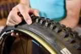 Als nächstes setzt man den Reifen zunächst mit einer Wulst auf die Felge. Hierbei ist zwingend auf die richtige Laufrichtung des Reifens zu achten. Ästheten sorgen für die gleiche Position der Reifenbeschriftung zum Ventil.
