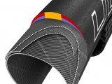 Top-Rennradreifen im Schnittbild: Der gelbe Streifen an der Lauffläche sorgt für lange Haltbarkeit, die roten Seitenpartien bieten hohe Kurvenhaftung. Die blaue Gummischicht darunter ermöglicht geringen Rollwiderstand.