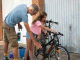 Unter Anleitung wird das Kinderfahrrad sauber gemacht.