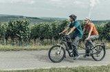 Radelndes Paar mit der Kraft von drei: Tandems bieten ohnehin flotten Fahradspaß, doch mit Zusatzantrieb wird das zweisame Radeln noch einmal schneller und komfortabler.