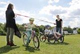 """Eine einfache Übung für die Radbeherrschung ist """"Fahrrad-Limbo"""": Wer schafft es, sich auf dem Rad klein genug zu machen, um berührungslos unter dem Flatterband durchzukommen?"""