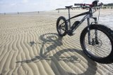 Die optimale Ausrüstung für einen Radtour auf nassem Sand: ein kräftiger Zusatzantrieb und Vier-Zoll-Reifen.